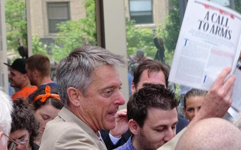 Bristol District Attorney C. Samuel Sutter carried a Bill McKibben article on climate change outside the Fall River court on Monday