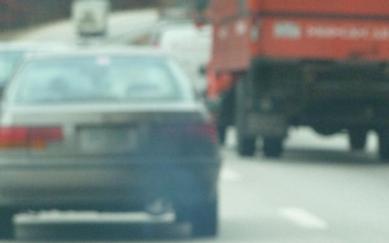 Exhaust pouring out of a car covering the back of it in black